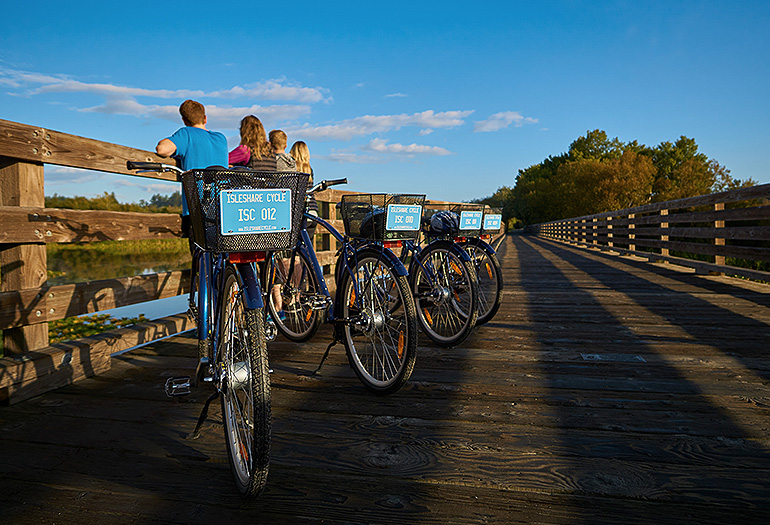 Family with bicycles stopped on bridge to see scenery