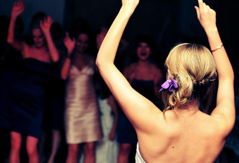 Bride tossing bouquet at wedding reception